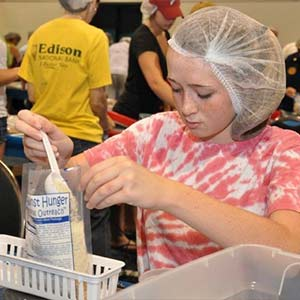 Girl Packaging Food | Meals of Hope Marco Island - Meal Packing to End Hunger