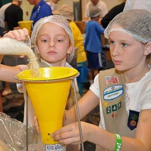 Two Girls Measuring Food | Meals of Hope Marco Island - Meal Packing to End Hunger